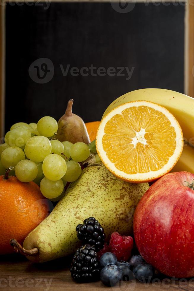frash fruit, sinaasappel, appel, banaan, peer, druiven tegen schoolbord foto