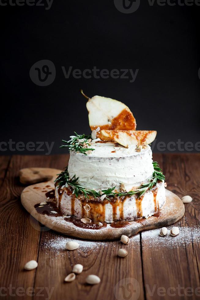 zelfgemaakte taart met peer, rozemarijn en pistachenoten op tafel foto