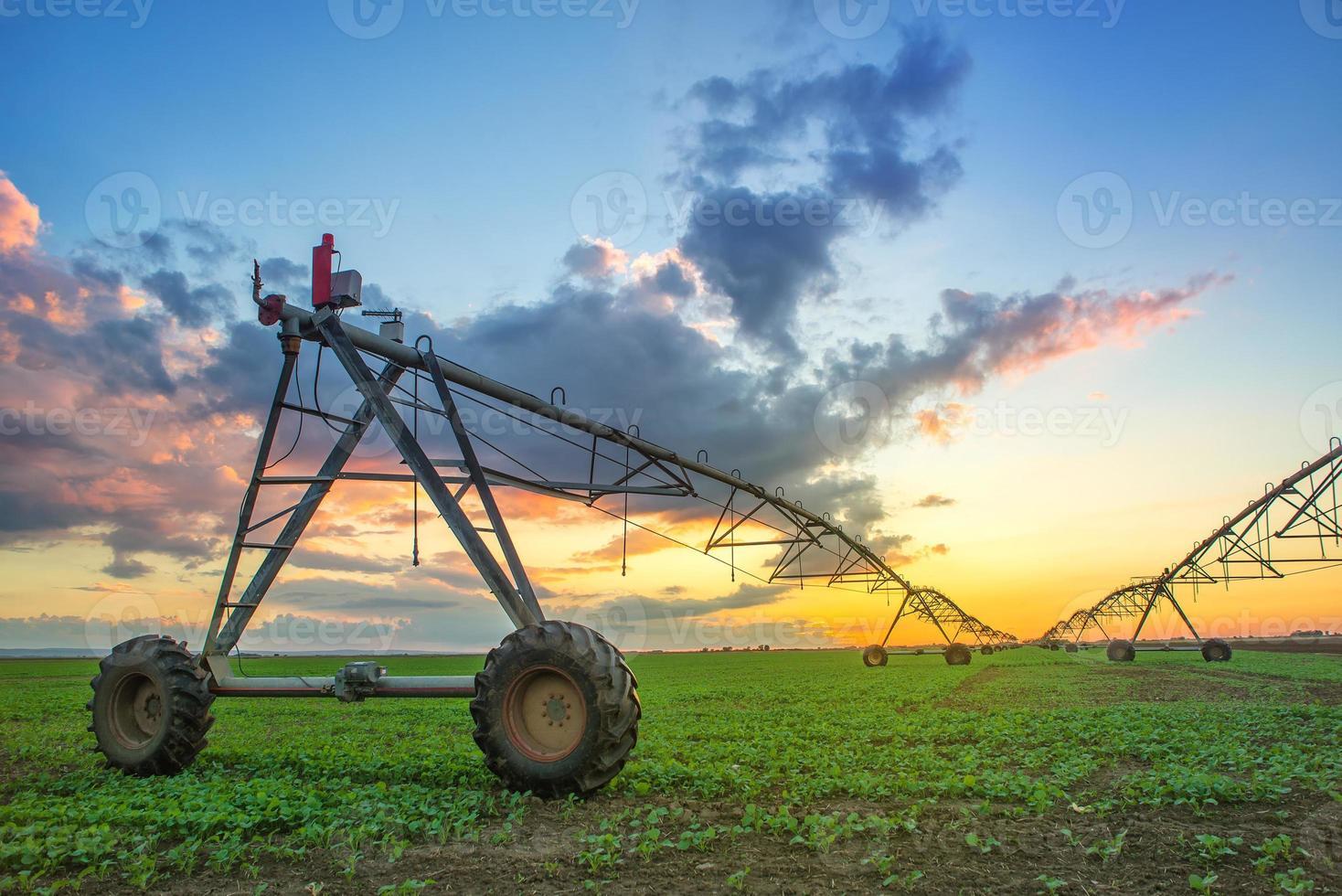 geautomatiseerd landbouwirrigatiesysteem bij zonsondergang foto