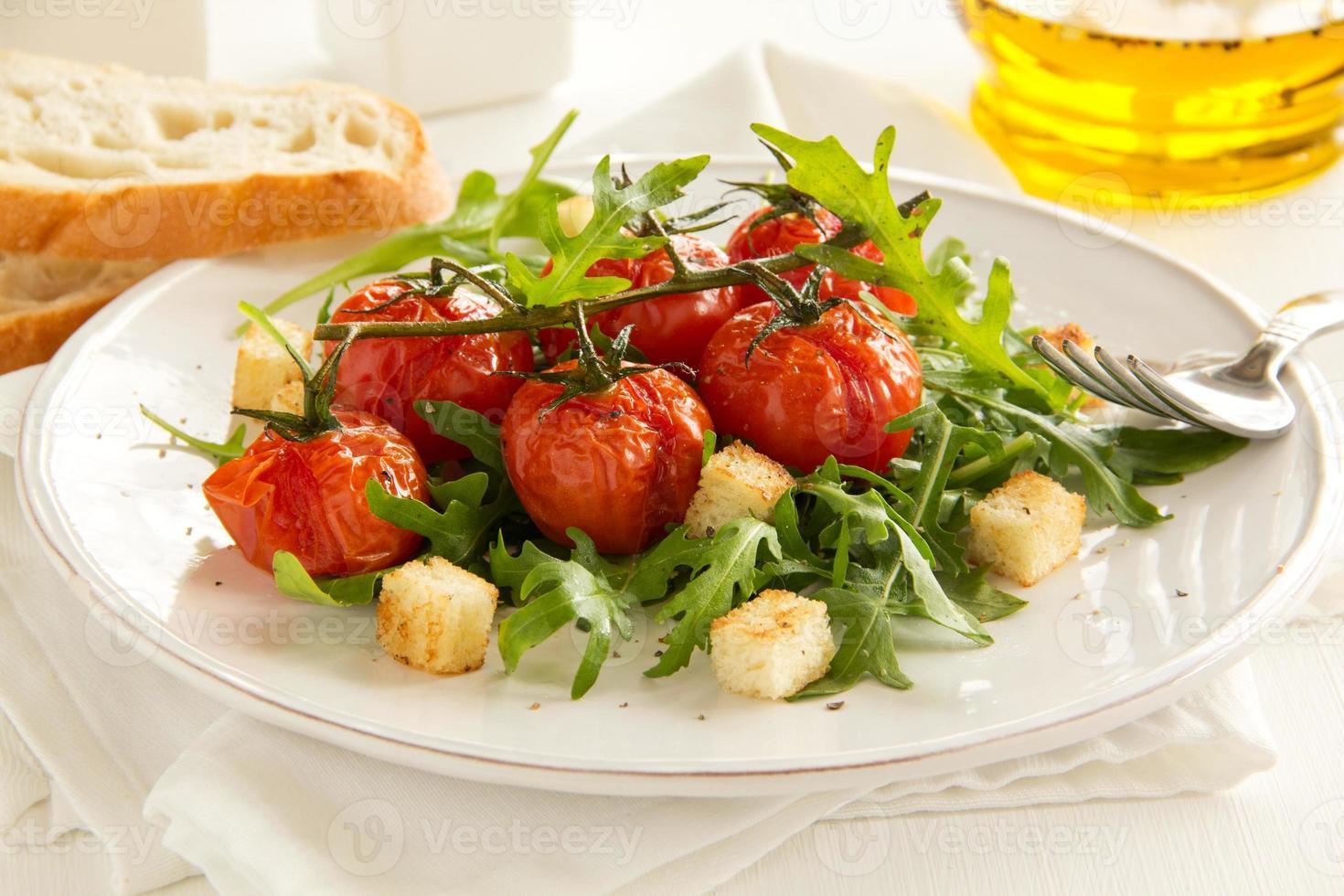 gegrilde tomaten met een salade van rucola en croutons. foto