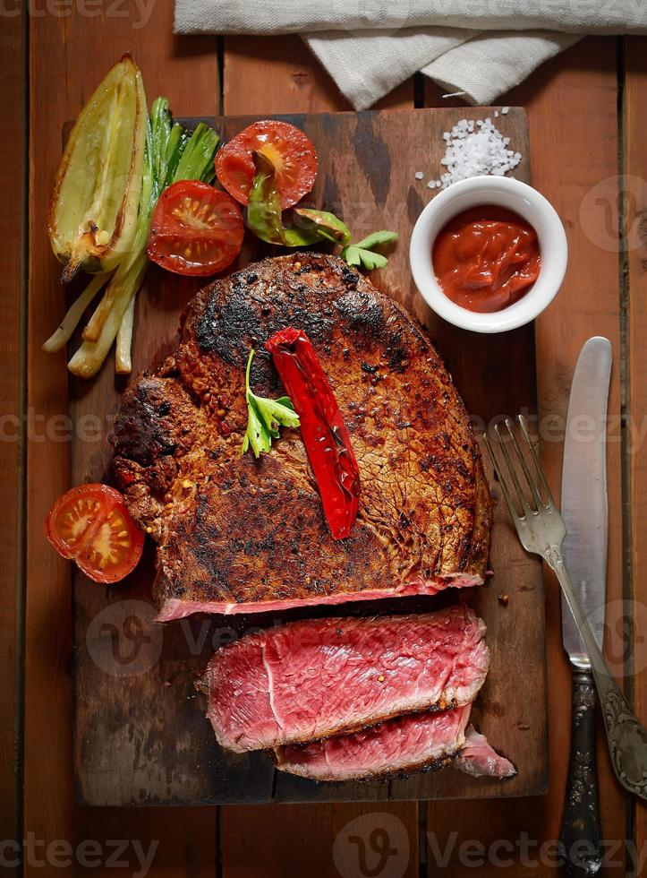 biefstuk op de houten achtergrond met geroosterde groenten foto