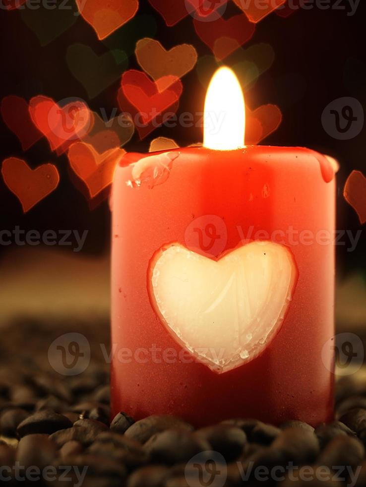 rode kaars en koffie op de tafel. harten op achtergrond. foto