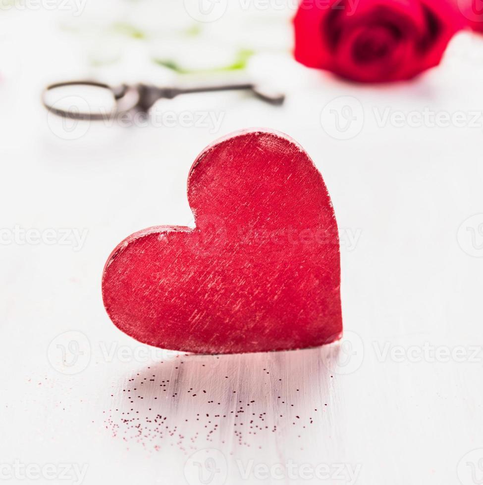 groot rood houten hart over roos en sleutel, Valentijnsdag foto