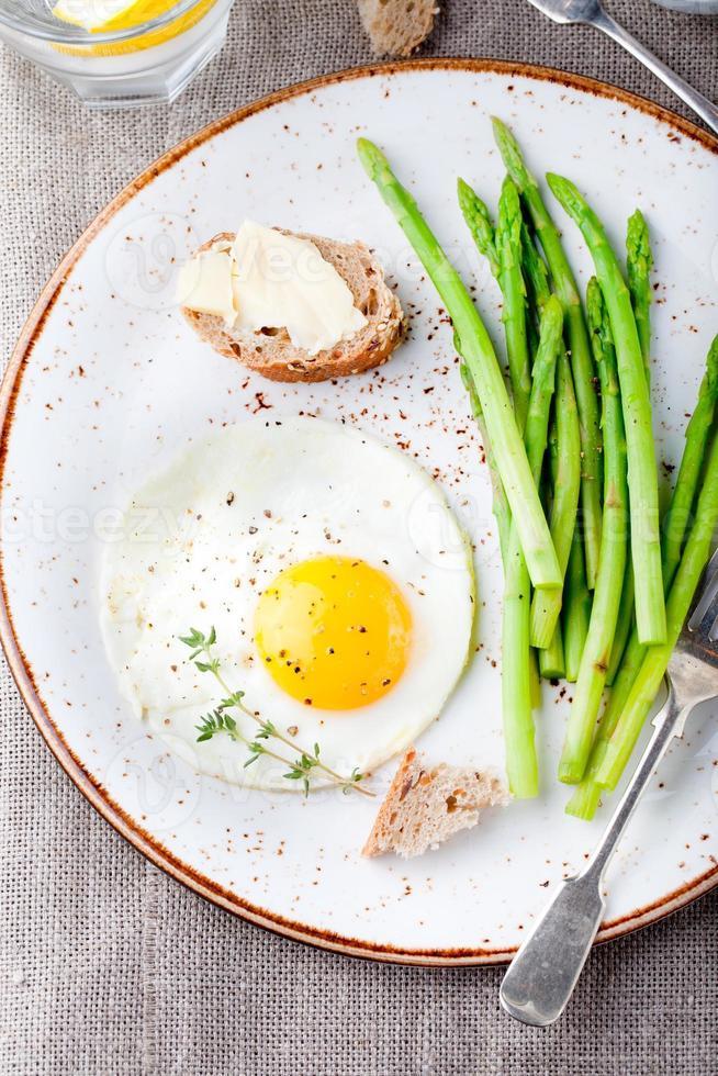 groene asperges, gebakken ei en brood met boter. foto