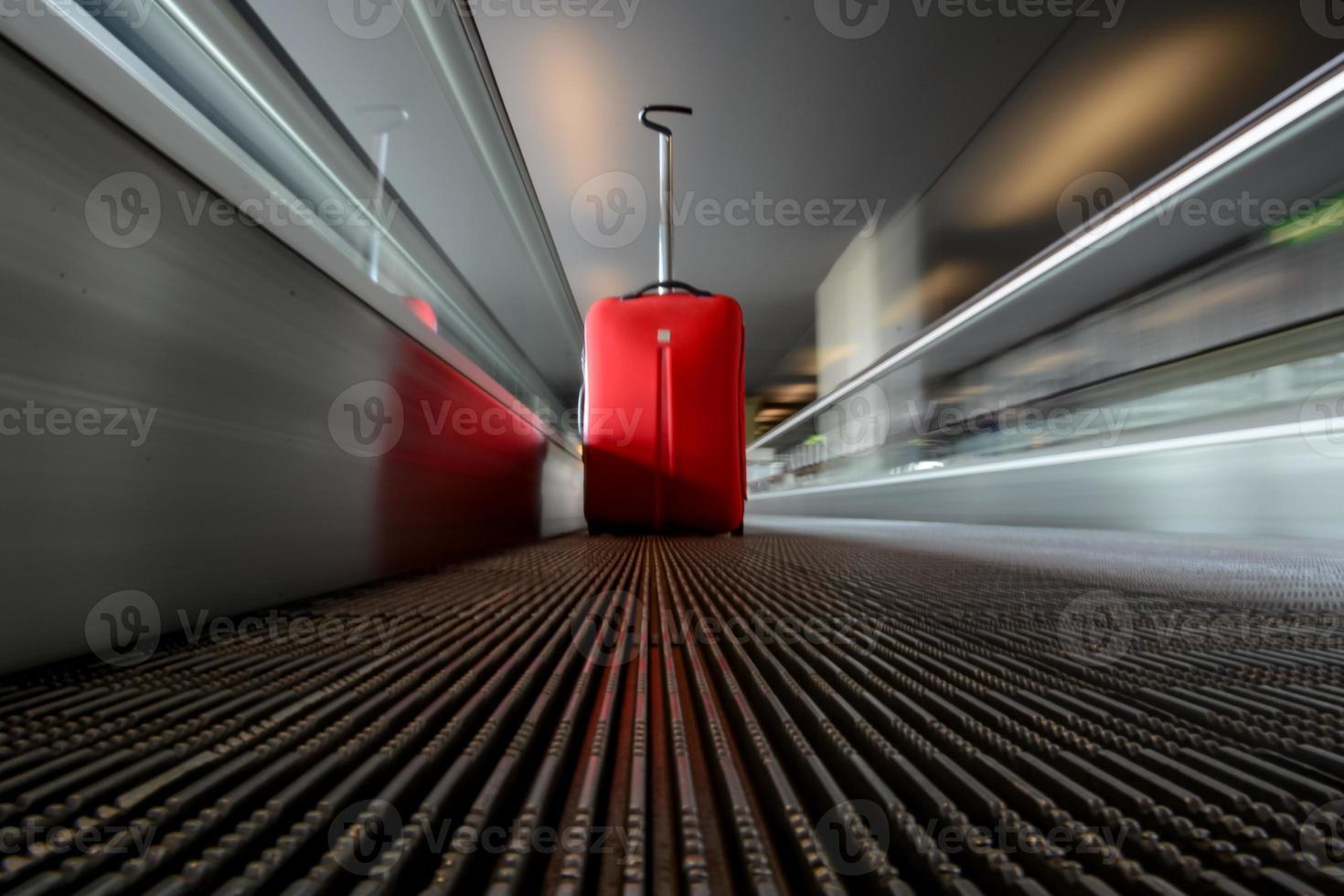 wazig bewegende roltrap met rode trolley in luchthaven foto