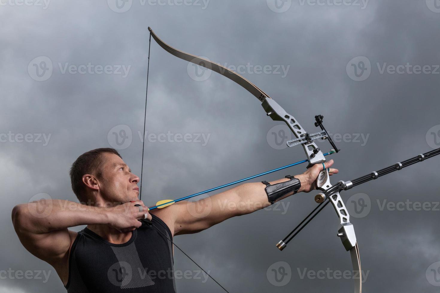 een mannelijke boogschutter die een schot met zijn boog en pijlen neemt foto
