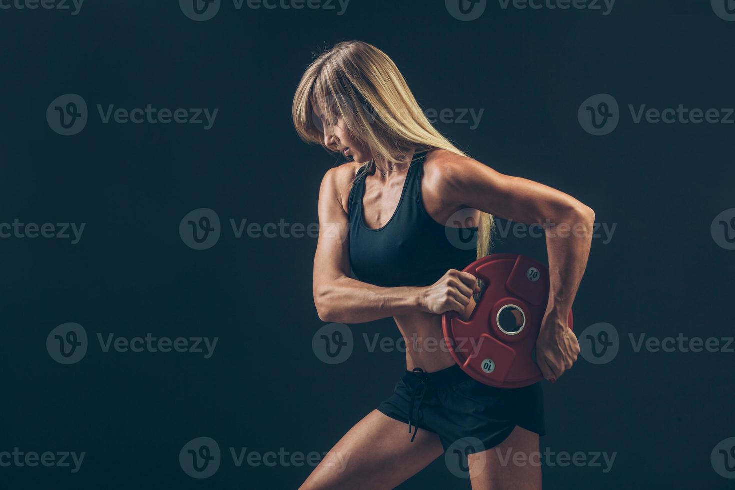 fitness vrouw die gewichtheffen doet door zware gewichten op te heffen foto