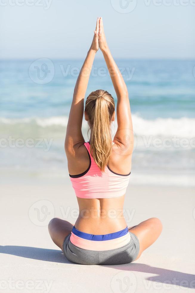 fit vrouw doet yoga naast de zee foto