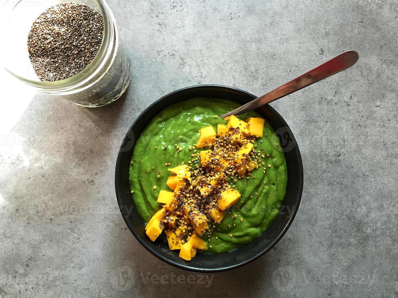 groene smoothiekom met gehakte mango en chiazaad foto