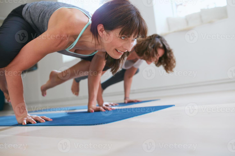vrouwen die yoga handstand doen - bakasana foto