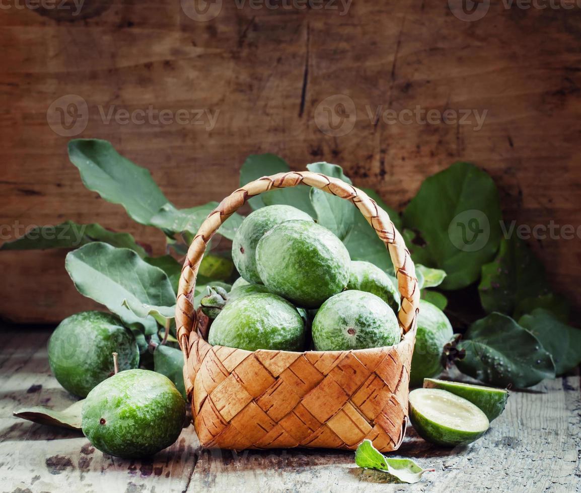 rijpe groene feijoa met bladeren in een rieten mand foto