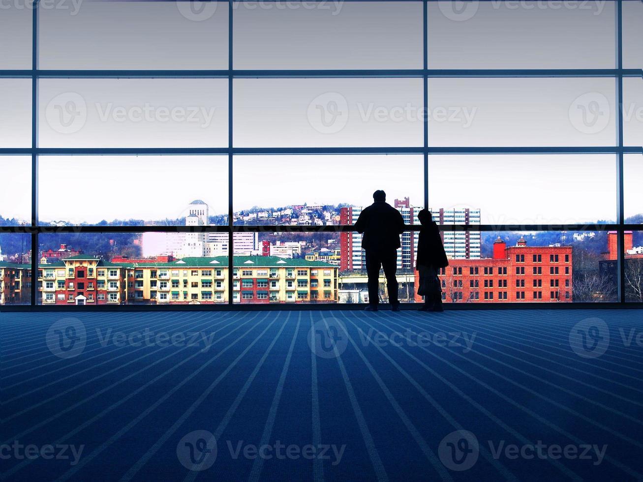 een groot raam waar twee mensen uitkijken naar de stad foto