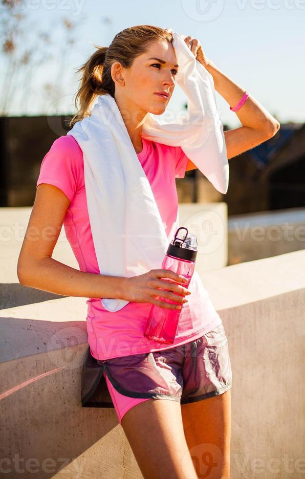 de geschiktheidsvrouw veegt gezicht met handdoek af foto