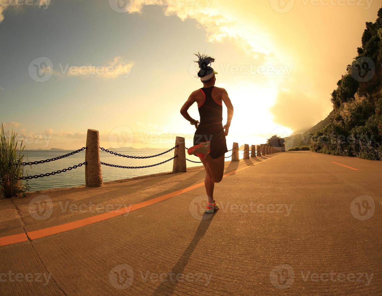 jonge fitness vrouw die op zonsopgang trail aan zee foto