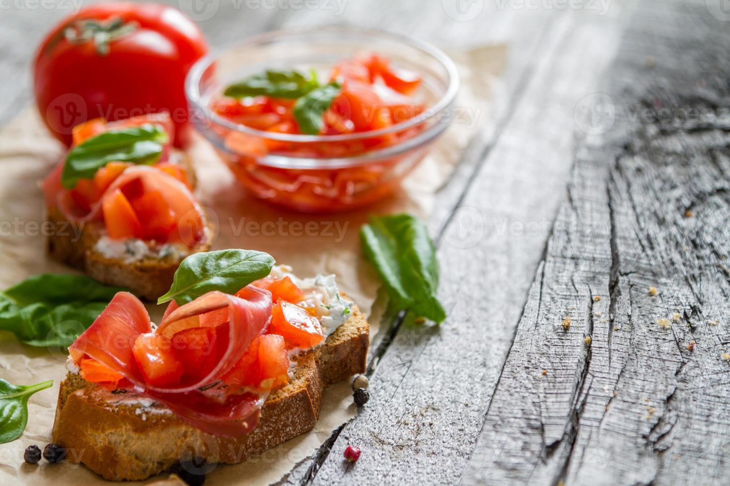 tomatenbruschetta en ingrediënten - brood, tomaat, hamon foto