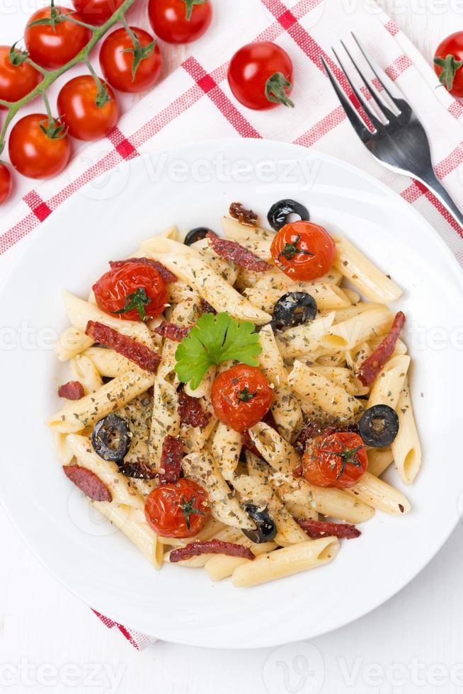 pasta met worst, tomaten en olijven, bovenaanzicht foto
