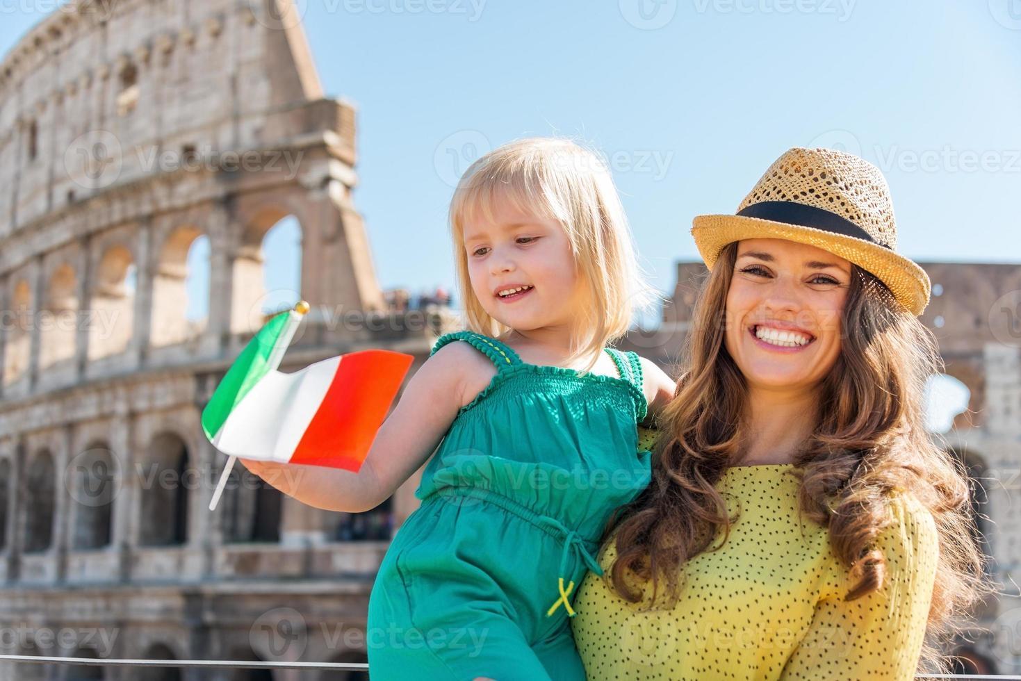 lachende moeder en dochter zwaaien Italiaanse vlag door colosseum foto