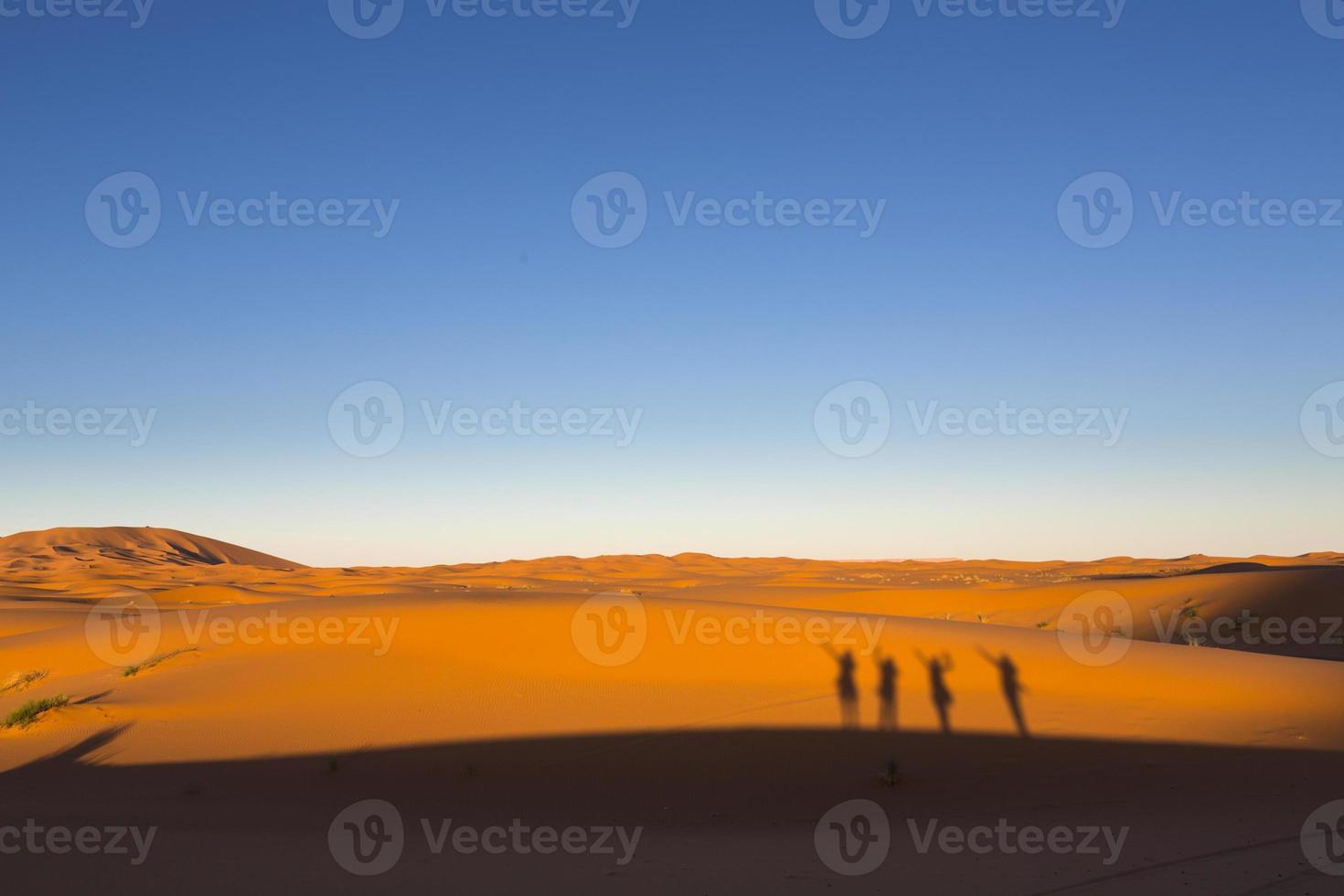 schaduwen van gelukkige mensen op duinen, woestijn Sahara Marokko, Afrika foto
