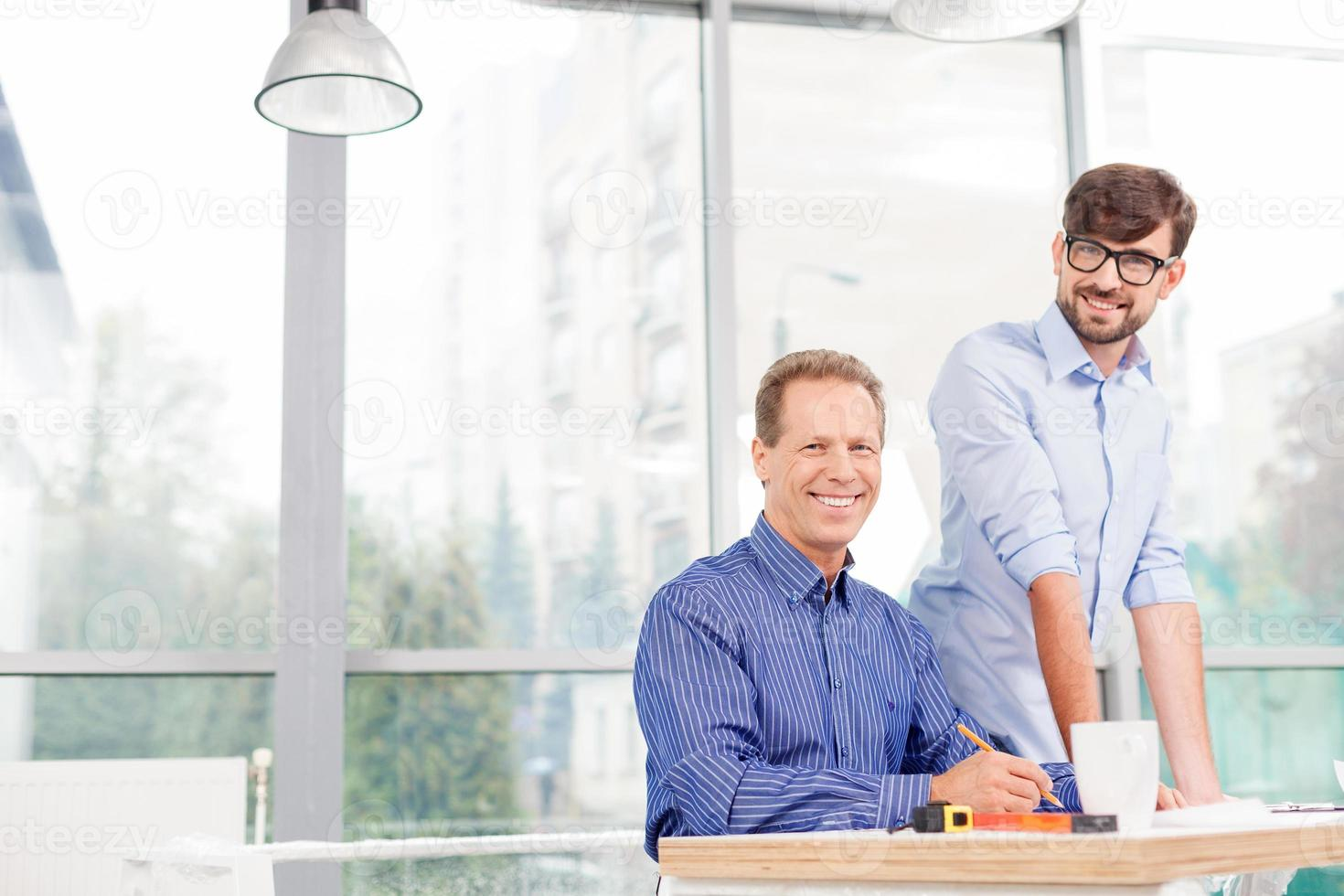 vrolijke mannelijke arbeiders bespreken het bouwplan foto