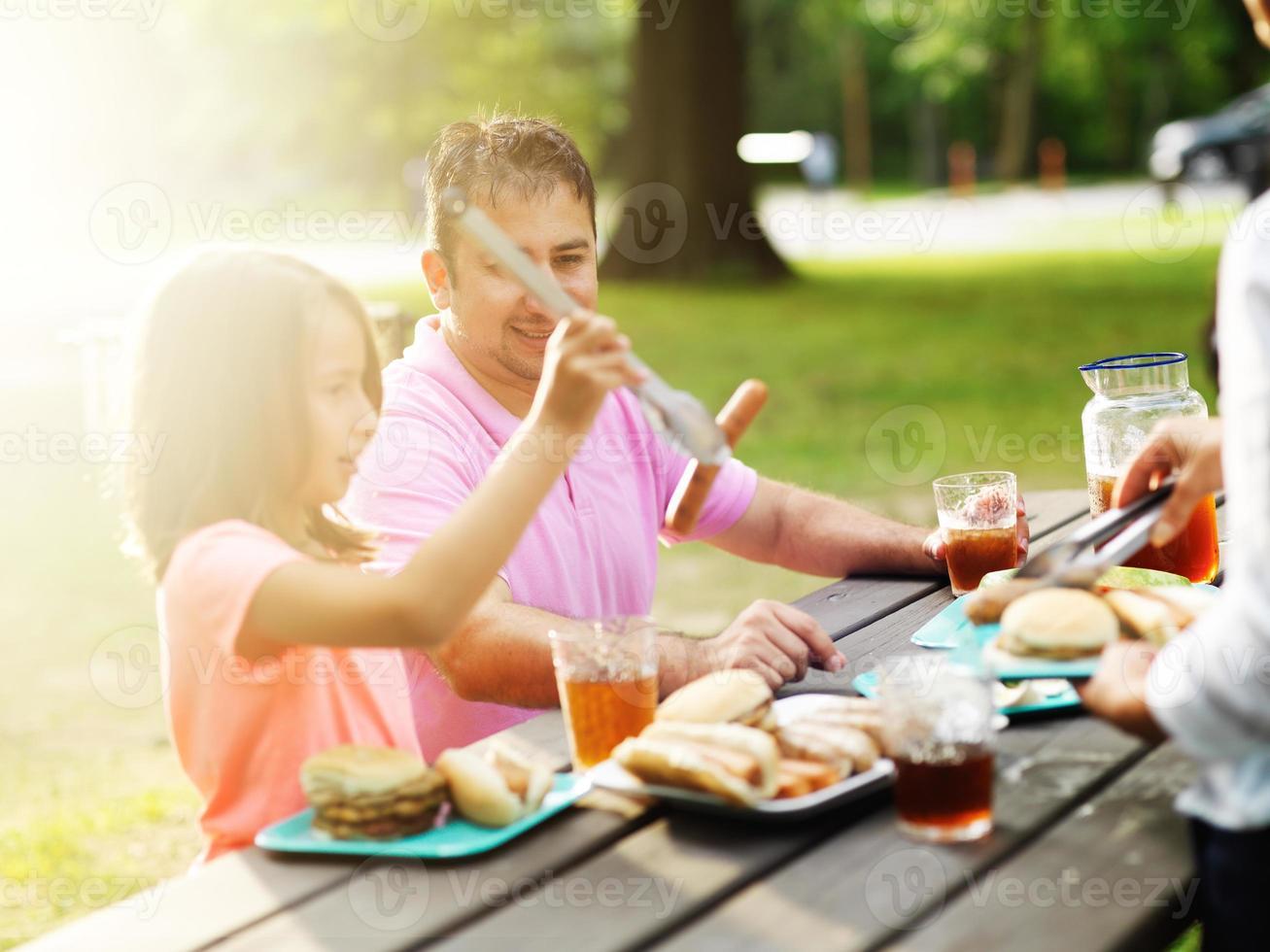 vader en dochter samen eten bij barbecue cookout foto
