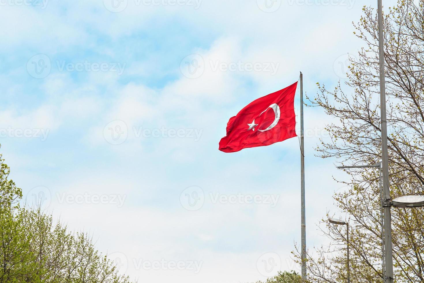 wuivende vlag van Turkije onder de blauwe hemel foto