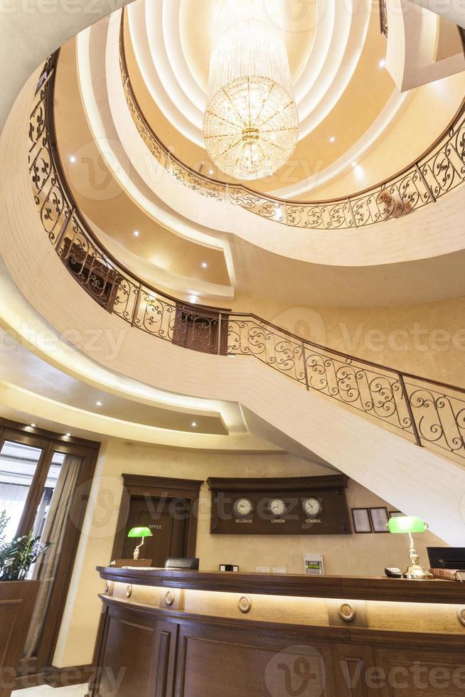 luxe hotel lobby receptie met wenteltrap en kroonluchter foto