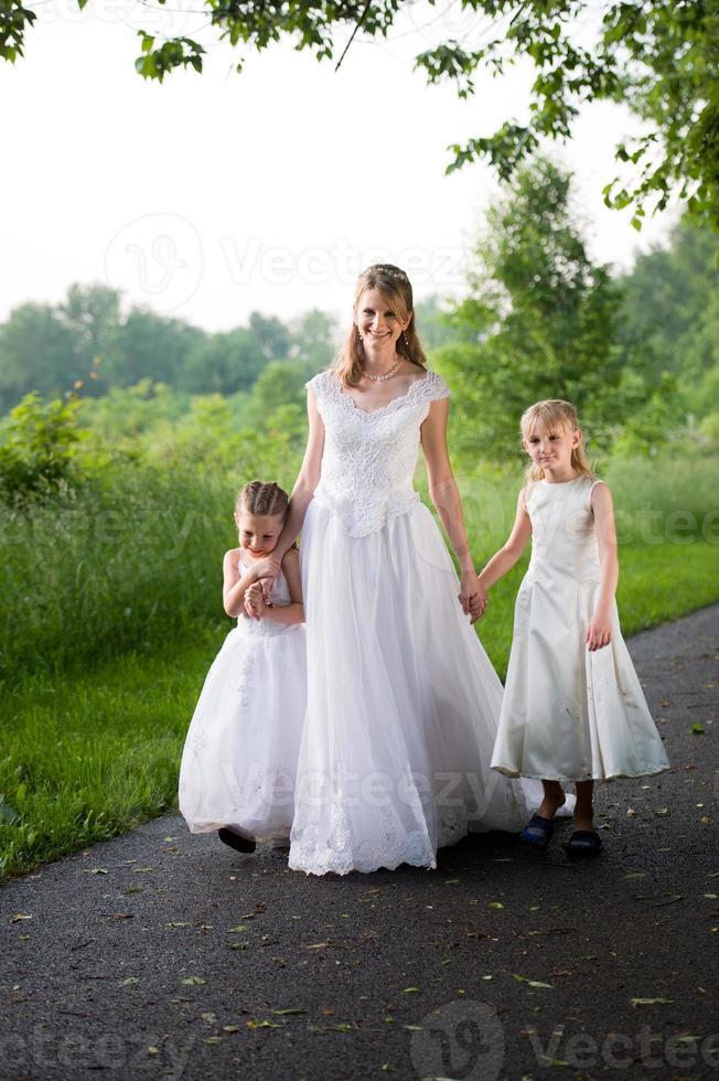 bloemenmeisjes met volwassen bruid lopen beboste pad foto