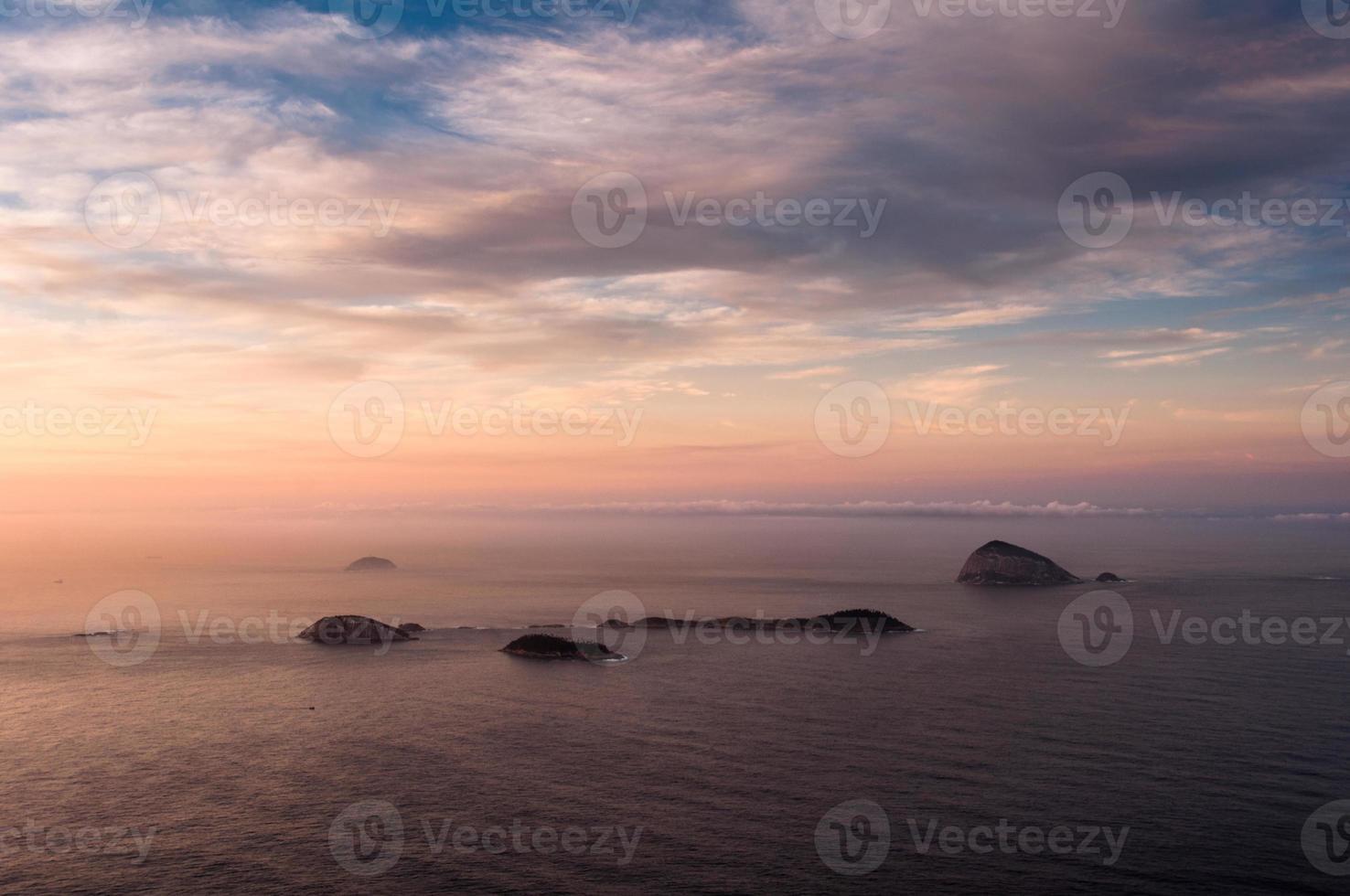 uitzicht op de oceaan bij zonsopgang met eilanden in de horizon foto