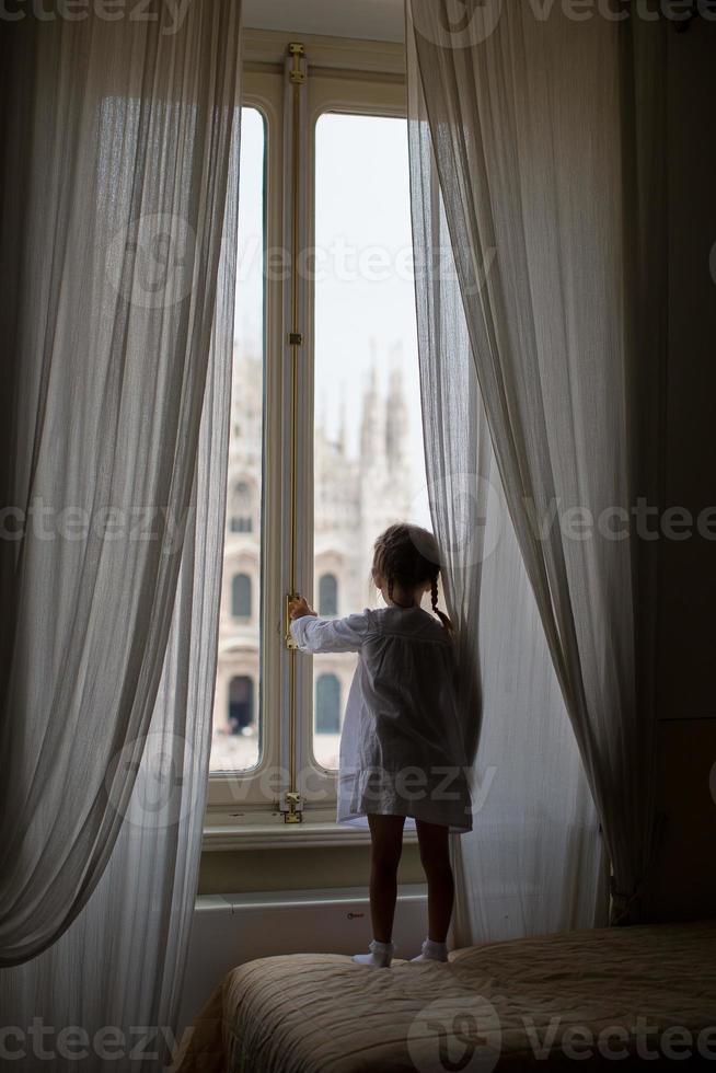 schattig klein meisje kijkt uit raam duomo, milaan, italië foto