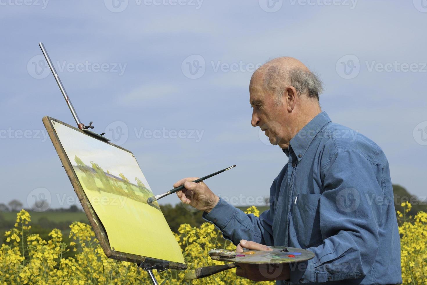 senior mannelijke kunstenaar schilderen in een veld. foto