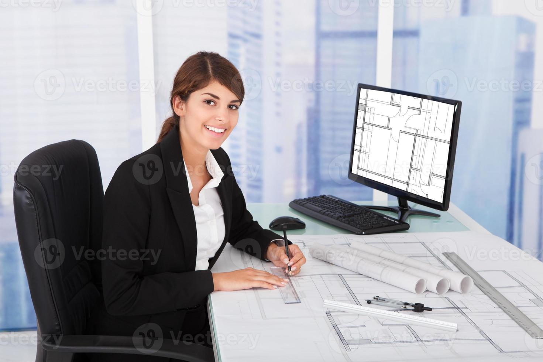 vrouwelijke architect bezig met blauwdruk aan balie foto