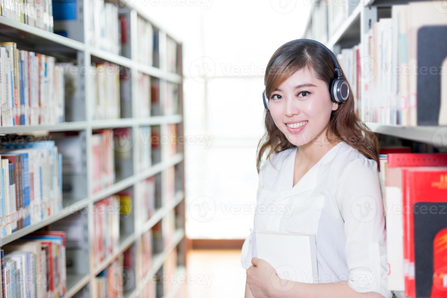Aziatische mooie vrouwelijke student portret in bibliotheek foto
