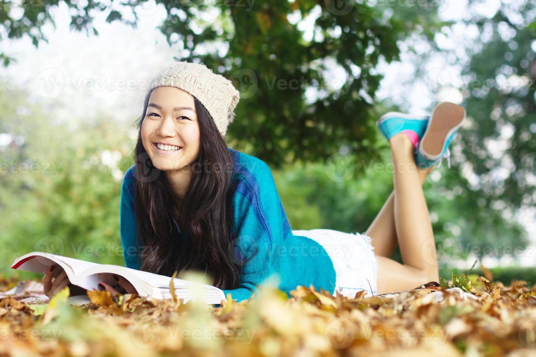lachende jonge Aziatische vrouwelijke student buitenshuis lezen foto