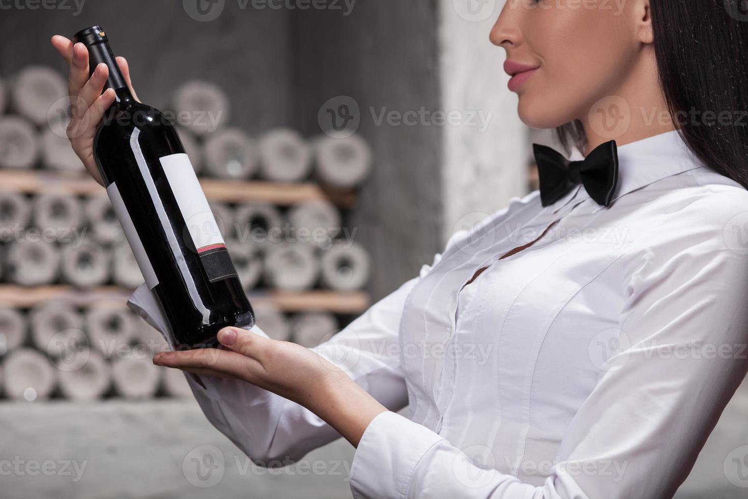 vrolijke vrouwelijke sommelier kiest voor perfect drankje foto