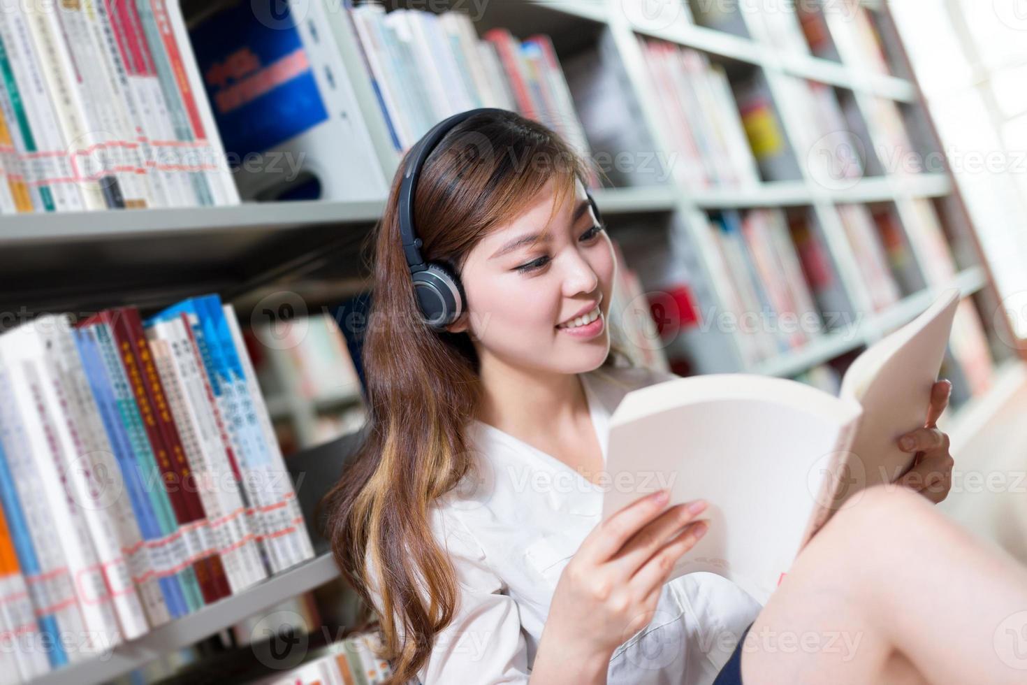 Aziatische mooie vrouwelijke studentenstudie in bibliotheek foto