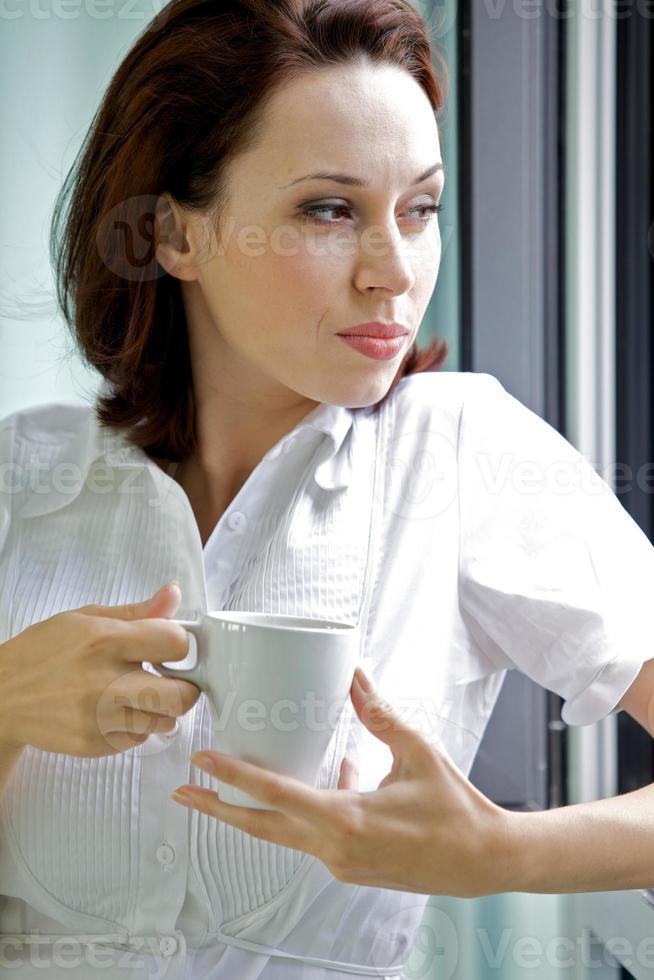 jonge vrouw koffie drinken in de ochtend foto