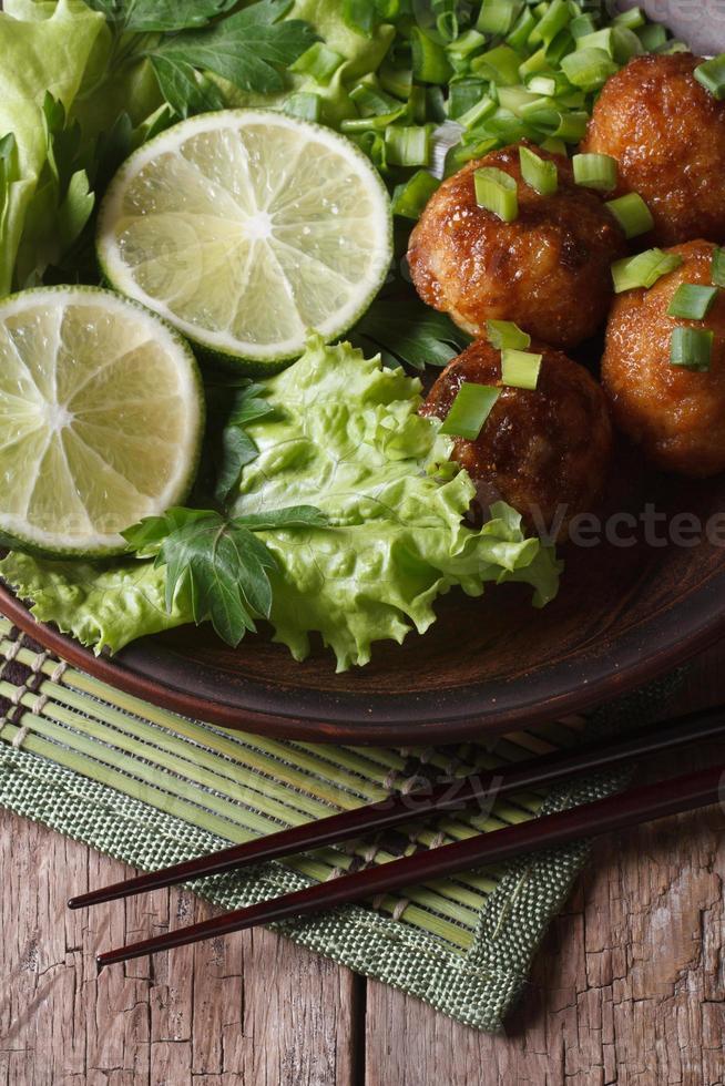 visballetjes met limoen en salade en eetstokjes close-up. verticaal foto
