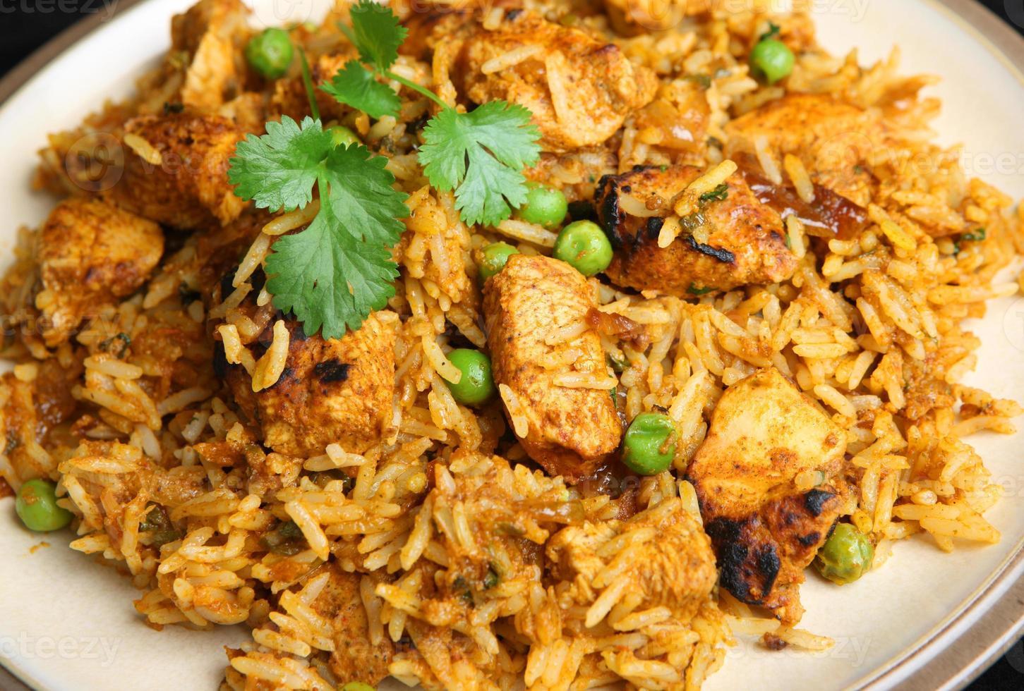 heerlijke Indiase kip tikka biriyani op witte plaat foto