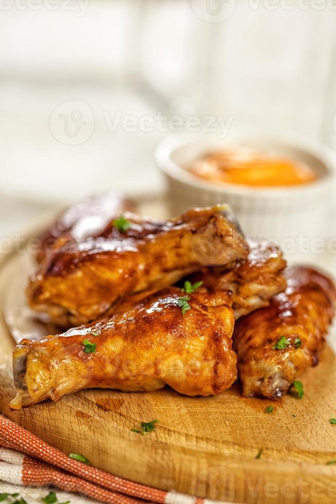 Buffalo kippenvleugels op houten plaat met BBQ-saus foto