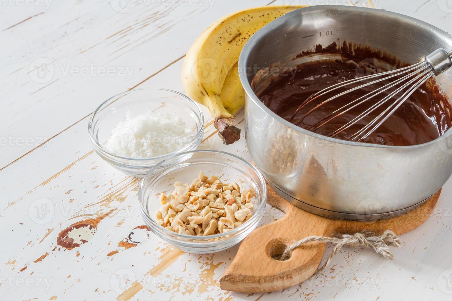 banaan pops voorbereiding - banaan, chocolade, noten, kokospoeder foto