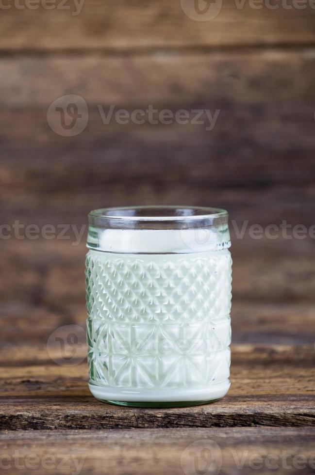 glas melk op een houten tafel foto