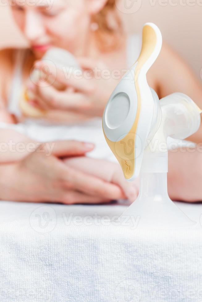 handmatige borstkolf en moeder die een pasgeboren baby voedt foto