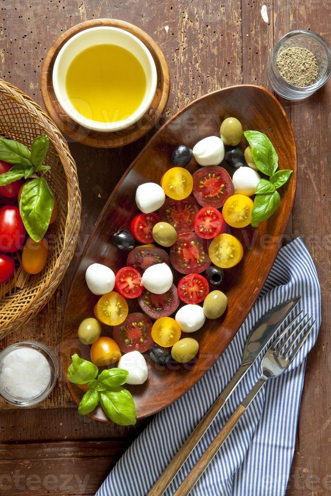 salade met gekleurde tomaten, kleine mozzarella, groene olijven en b foto