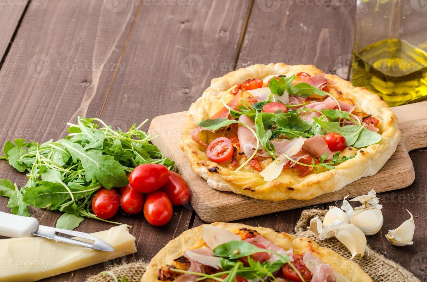 Italiaanse pizza met parmezaanse kaas, ham en rucola foto