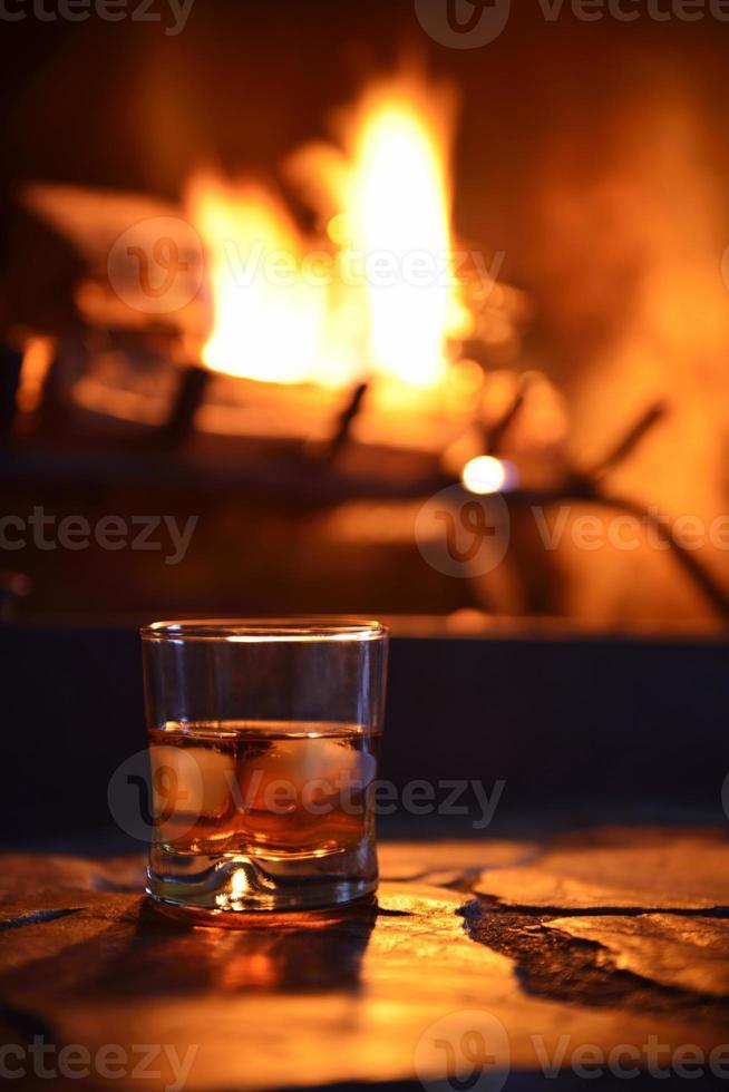 glas sterke drank met ijsblokjes en open haard foto