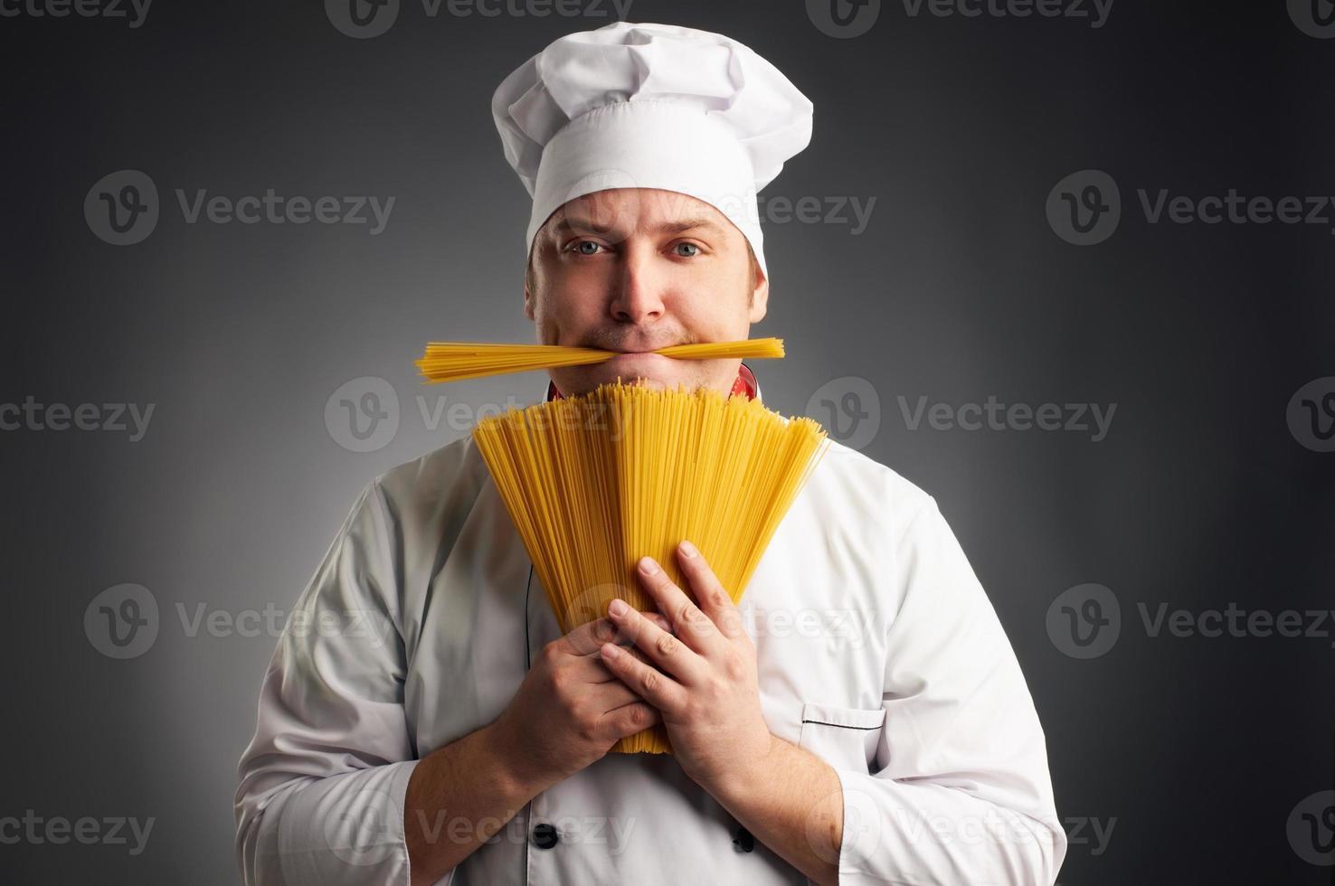grappige kok met spaghetti in zijn mond foto