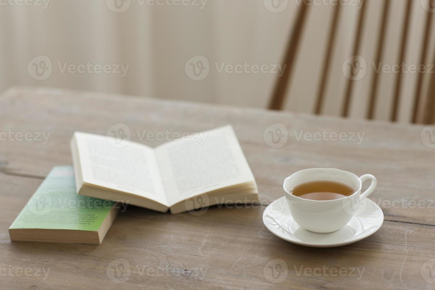 een kopje thee op een houten tafel met boeken foto
