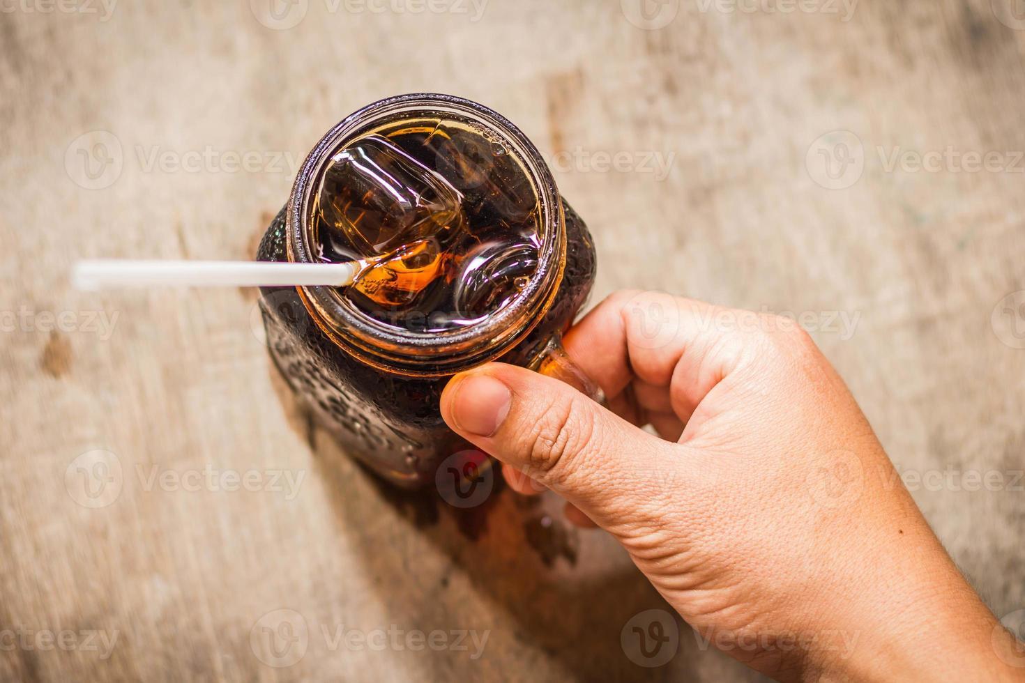 hand met cola in glas met ijs op tafel foto