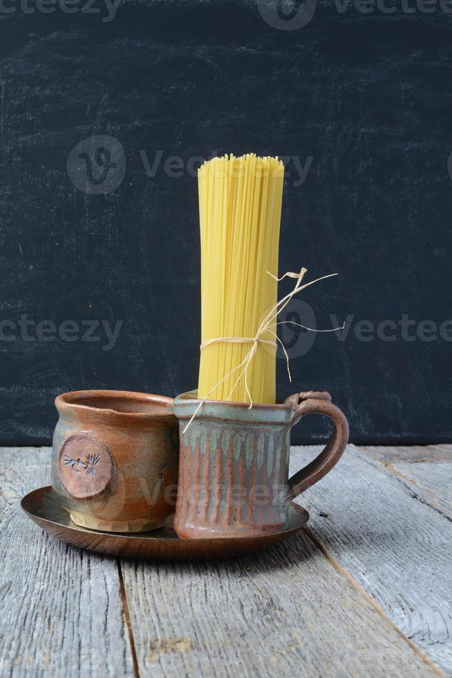 ruwe spaghetti in aardeslijtage op rustieke houten achtergrond foto