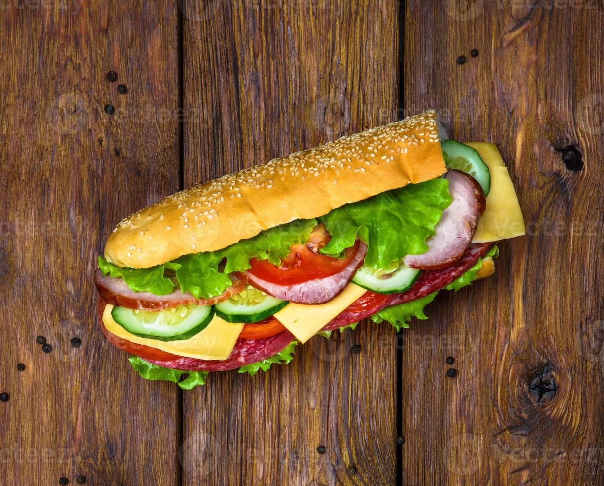 sandwich met vlees en groenten op hout foto